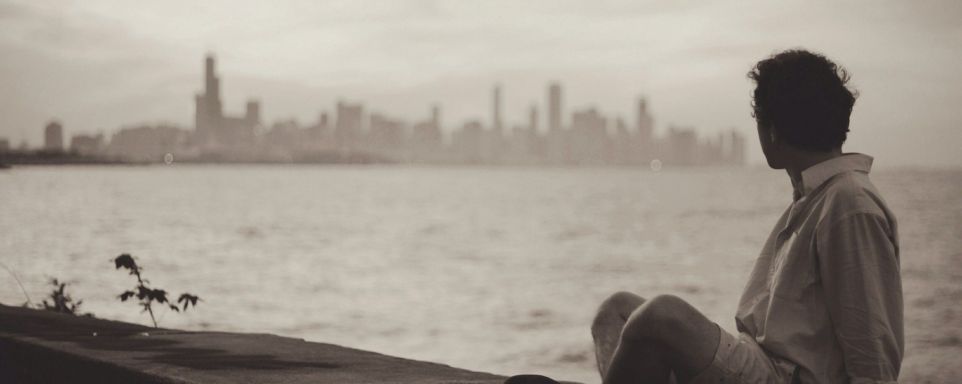 seaside,man,sitting,relax,wait,wall,waiting,lifestyle,casual,thinking,alone,single,young,person,adult,male,people,grunge,guy,waterfront,city,buildings,skyline,view,looking,watching,DON CHARISMA